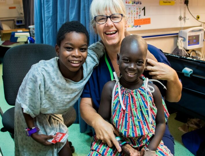 Robyn Ferguson, Ward Nurse,  with two young patients on B Ward.
